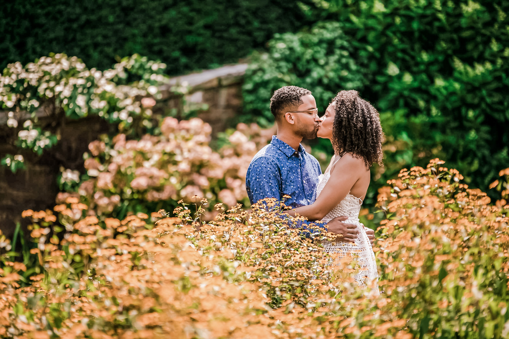 Couple kissing while being surrounded by foliage