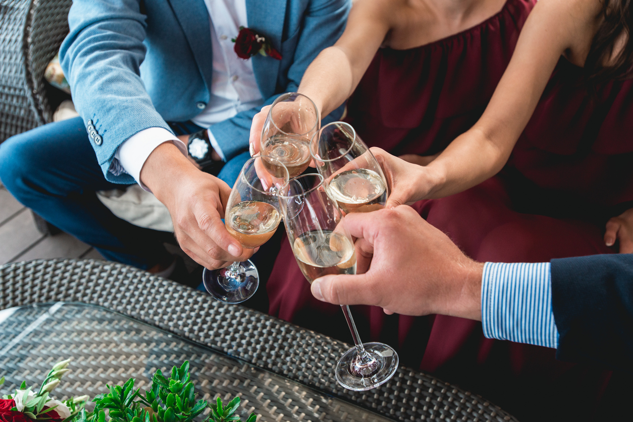 couple and bridal party holding white wine glasses