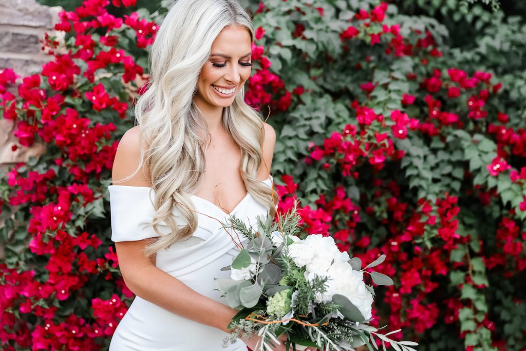 smiling bride in an off-shoulder wedding dress holding a white rose bouquet
