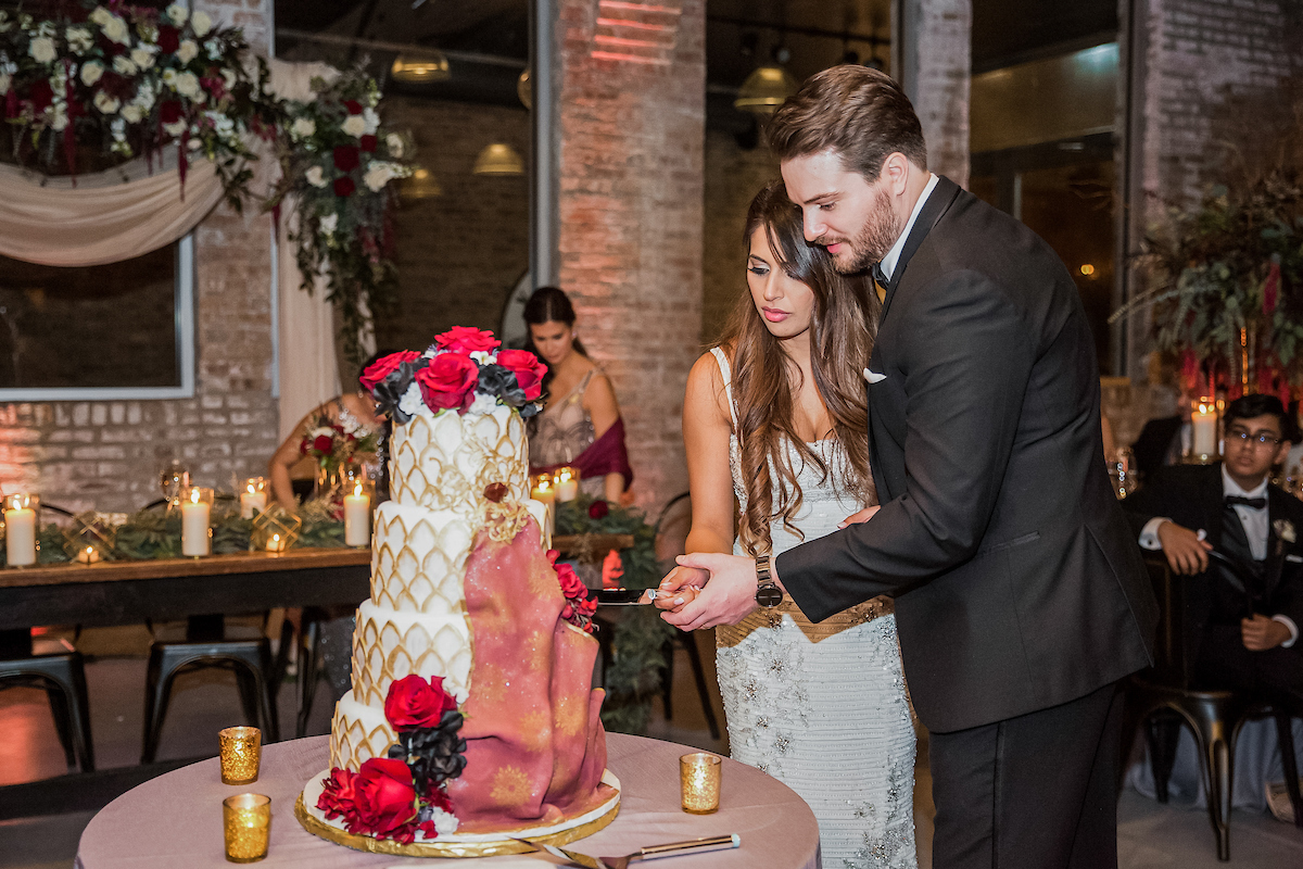 Handsome groom and pretty bride cutting a four tiered wedding cake decorated with roses