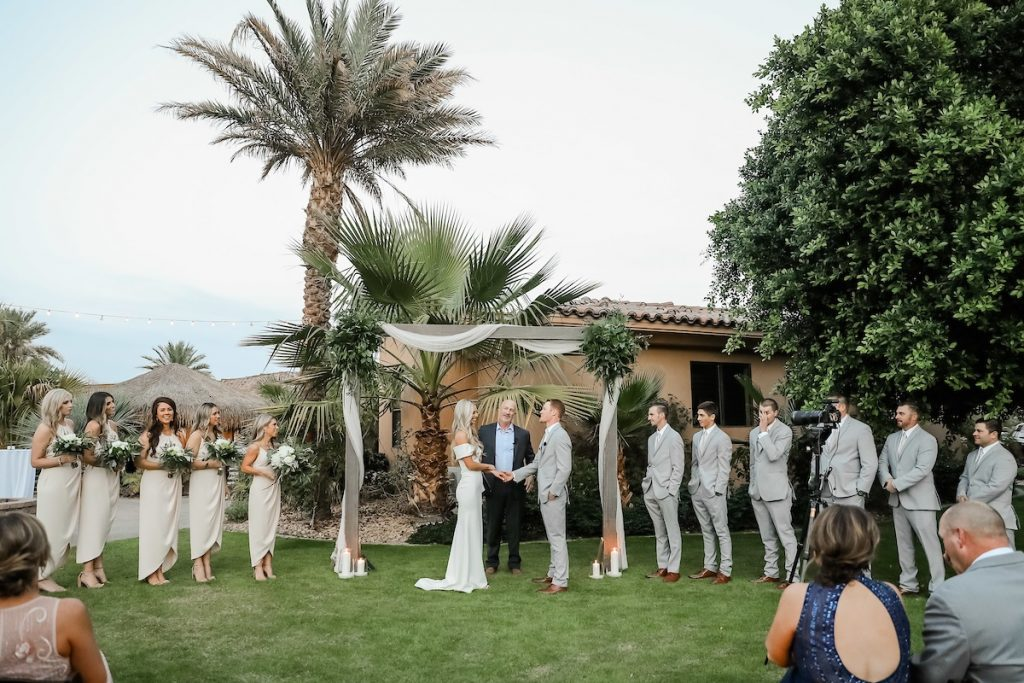 couple holding hands getting married by the officiant at the altar surrounded by the bridal party on either sides in an outdoor wedding ceremony setup